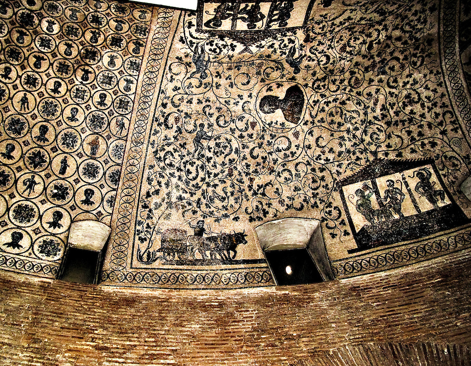 Sta Costanza, black and white mosaic detail in the curved ambulatory ceiling; 4th century.  Complicated design of grapevines interspersed with realistic figures doing the grape harvest, busts of other figures, and medallions with a variety of insets..