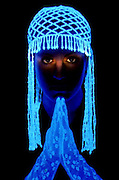 Portrait of a young girl with glowing headpiece and gloves praying.Black light