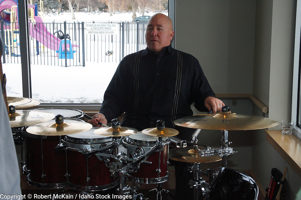 IDAHO. Boise. Jewish folk musician playing drums at Bat Mitzvah celebration. December 2008. #pa080713 MR