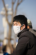 Cyclist wears face mask in heavy traffic polution, Beijing, China