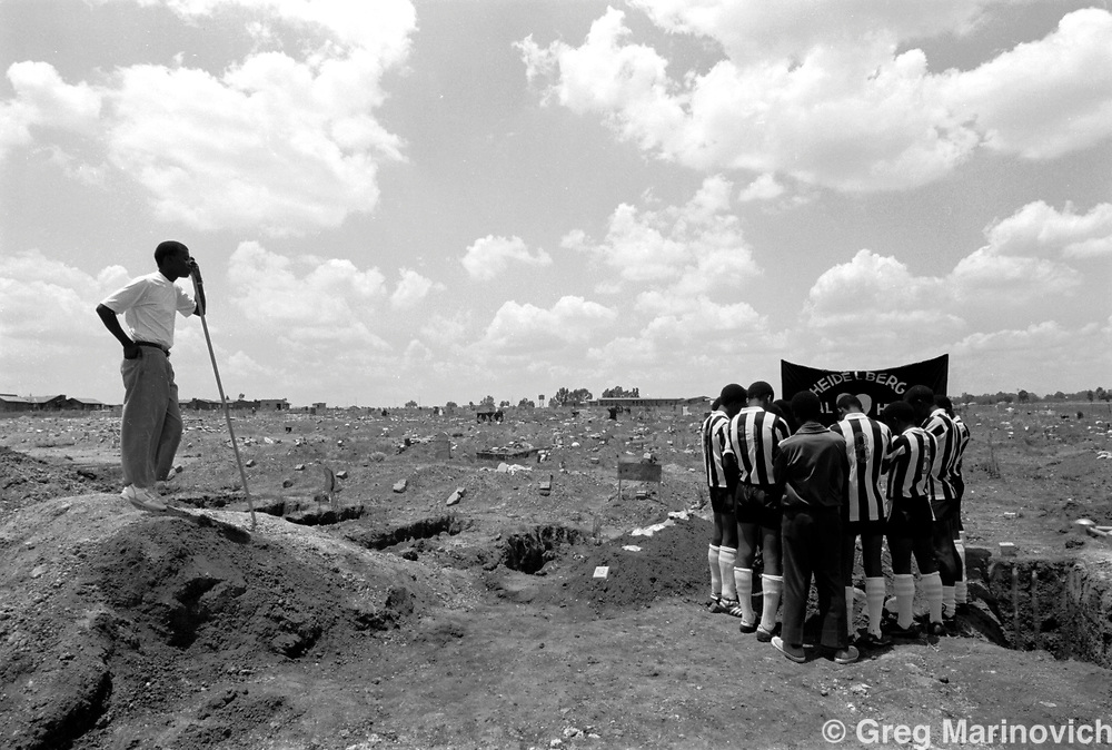 IPMG0088 South Africa, Ratunda, 1992..A soccer team say farewell to their teammate Phillip Monaheng (20) killed in crossfire between Inkatha and the ANC in Ratunda township 60km south of Johannesburg, 28 Nov 1992. Thousands of people, both civilians and combatants died in the so-called Hostel War from 1989-1995. The conflict at Ratunda also involved unions vying for scarce jobs at the meat processing factory..Photograph by Greg Marinovich/South Photographs