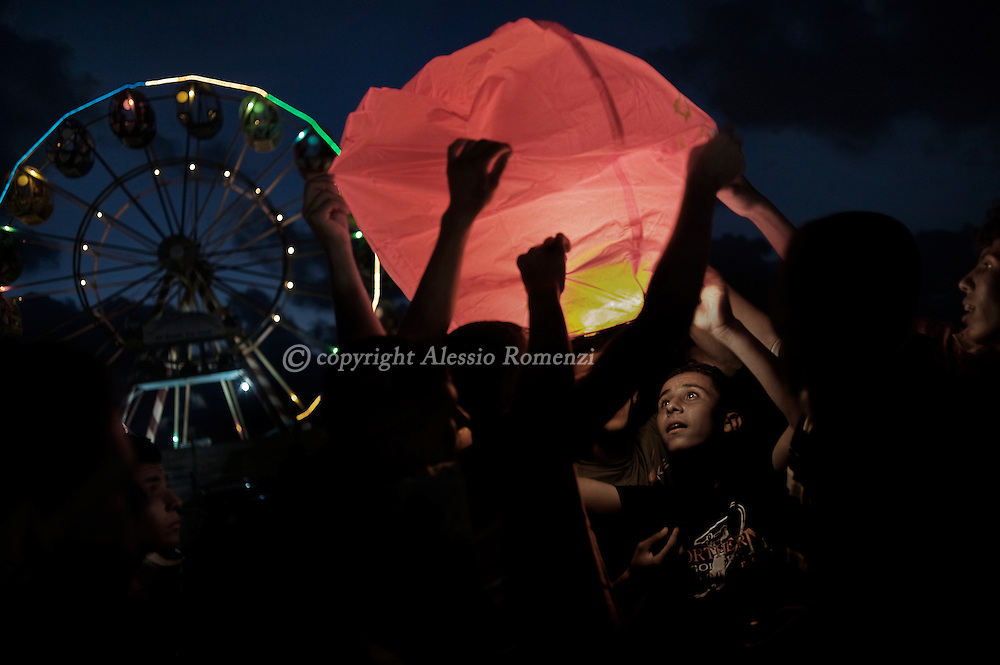 Young Palestinian attempt to light a hot air lantern September 11, 2010 outside an amusement park on the outskirts of Gaza City on the second day of the Eid al-Fitr, as Muslim families continue to celebrate the end of the holy fasting month of Ramadan.© ALESSIO ROMENZI