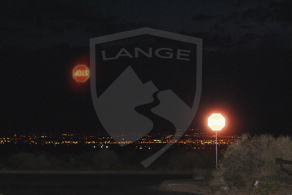 albuquerque night scene cityscape and stop sign with reflection created by light from on camera flash reflected internally on the lens barrel showing an interesting optical photographic effect