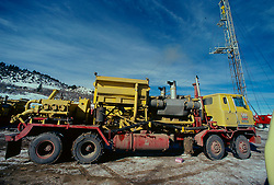 Stock photo of a large yellow fracking truck at a work site