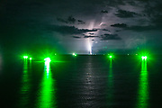13 May 2017. Hua Hin, Thailand.<br /> Fishing boats looking for squid sit off the coast of Hua Hin Thailand, as an electrical storm looms in the clouds above them. The fisherman use florescent green lights to help attract the squid to their boats.<br /> Photographer: Rick Findler