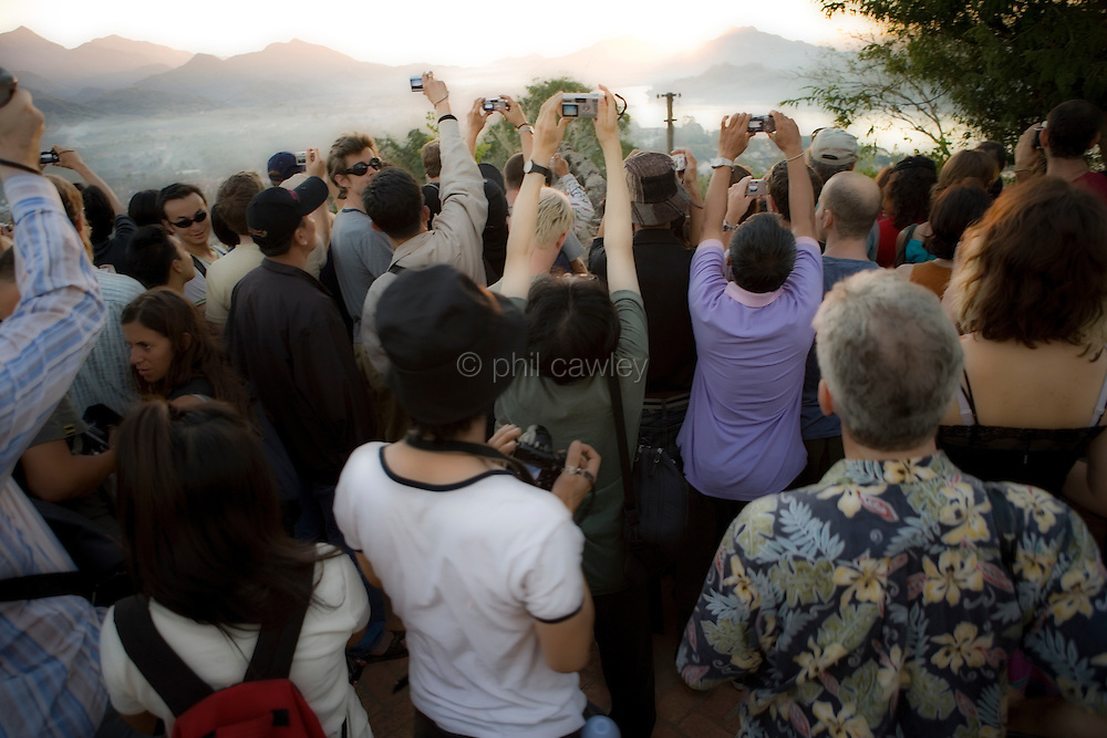 Crowds of people at the temple in Luang Prabang  Laos. Mount Phousi stupa The highest point in the  town, everyone trying to get a good shot of the  sunset over the mekong river