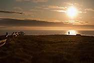 A photographer makes his way along the cliff at the Point Cabrillo Lighthouse property in Mendocino, California.