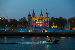 © Licensed to London News Pictures. 09/04/2020. London, UK. A police boat travels on the River Thames past light projections onto the Tower of London this evening in recognition and appreciation of National Health Service (NHS) and key workers during the ongoing COVID-19 coronavirus epidemic. Photo credit: Vickie Flores/LNP