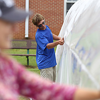 Zeke Dickey helps secure the plastic wrap to the new greenhouse under construction at Lawndale Elementary SChool Monday afternoon.
