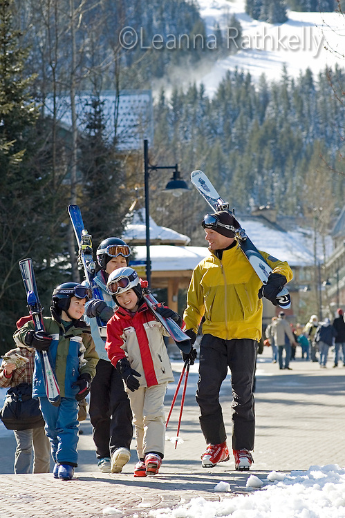 A family of skiers laugh with each other as they walk through Whistler Village on a sunny winter day.