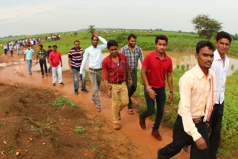 Fans make their way through the muddy fields to the stadium during the qualifier 1 match of the Oppo Champions League Twenty20 between the Northern Knights and the Southern Express held at the Chhattisgarh International Cricket Stadium, Raipur, India on the 13th September 2014<br /> <br /> Photo by:  Ron Gaunt / Sportzpics/ CLT20<br /> <br /> <br /> Image use is subject to the terms and conditions as laid out by the BCCI/ CLT20.  The terms and conditions can be downloaded here:<br /> <br /> <br /> http://sportzpics.photoshelter.com/gallery/CLT20-Image-Terms-and-Conditions-2014/G0000IfNJn535VPU/C0000QhhKadWcjYs