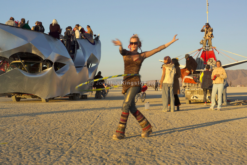 BLACK ROCK CITY, NV:  A hula hooper at sunrise on the playa in Black Rock City, Nevada.  In the art car behind the hooper there is a wedding taking place.