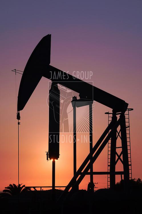 Sun setting behind an oil pump rig