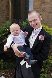 Portrait of groom holding baby boy,