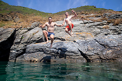 © Licensed to London News Pictures. 04/08/2018. St Austell, UK. Charlie Nicholson (left) and Sam Crofts (right) jump into the sea off the coast path near Gorran Haven, Cornwall during hot weather. Photo credit : Tom Nicholson/LNP