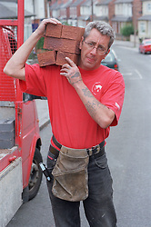 Builder carrying pile of bricks on shoulder,