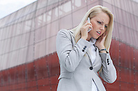 Frustrated businesswoman in suit conversing on cell phone against office building