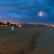 A firework flashes above Port Hueneme Beach as twilight sets in.