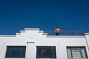 A shirtless man stands with his back to the street below on the rooftop of a bar, during cloudless blue skies of an English seaside resort,  9th July 2020, in Whitstable, Kent, England.