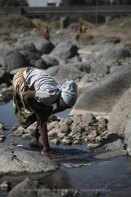 A woman washes in a river in the town of Dukem on the road to Nazet, Ethiopia. Such rivers are heavily relied upon by local people as water is scarce during the 9 months of the dry season.