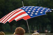 Visitors hold an umbrella decorated as an American flag at the National World War II Memorial, Washington, DC