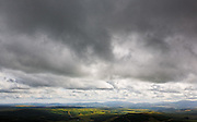 View west of fields in sunlight under a storm cloud from Benbrack near Cairnhead, Southern Uplands, Scotland