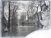 broken and eroding glass plate of flooded street with truck driving through the water Paris 1900s