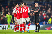 Arsenal players surround the referee at half time to question his decision to rule out handball during the Premier League match between Chelsea and Arsenal at Stamford Bridge, London, England on 21 January 2020.
