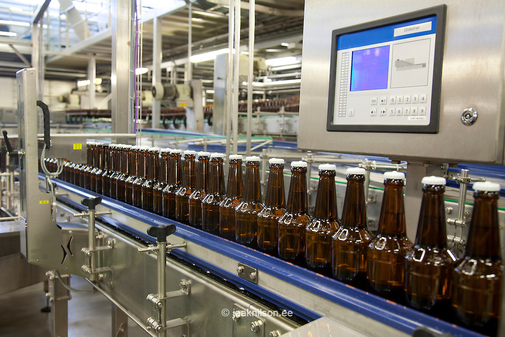Large machine with moving belts with rows of bottles. Bottling machine,  labelling and capping.