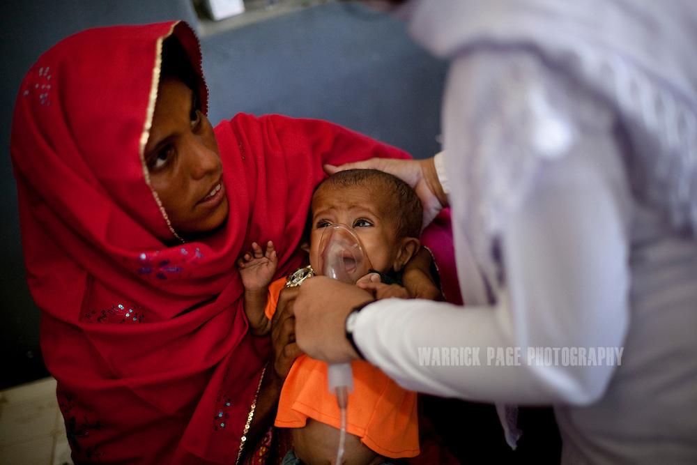 Umeera, 20, holds her child, , Umbreen,14 months, as a nurse applies a nebuliser at a nutrition stabilisation centre, on October 14, 2011, in Thatta, Pakistan. Umbreen was born low birth-weight and did not develop a full appetite and needed to be taken to a nutrition stabilisation centre. According to UN reports, hundreds of thousands of children in Pakistan suffer from severe-acute-malnutrition, with 15.1% of children experiencing acute malnutrition. Child malnutrition has breached emergency levels in Pakistan's Sindh province, after monsoon floods devastated the country's poorest region for a second year. Extreme poverty, poor diet and health, exposure to disease, and inadequate sanitation and hygiene annually produce alarming levels of malnutrition amongst children, but the floods have increasingly endangered an already vulnerable population. (Photo by Warrick Page)