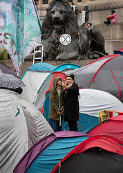 © Licensed to London News Pictures. 12/10/2019. London, UK.Two people take a selfie amongst Extinction Rebellion activists' tents as they continue their protests in Trafalgar Square after being moved by police from all other central London locations. XR activists calling on the government to act now on climate change have been protesting in the capital for six days. Photo credit: Peter Macdiarmid/LNP