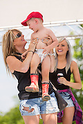 A mother holds up her son after he won the cutest red neck child competition during the 2015 National Red Neck Championships May 2, 2015 in Augusta, Georgia. Hundreds of people joined in a day of country sport and activities.