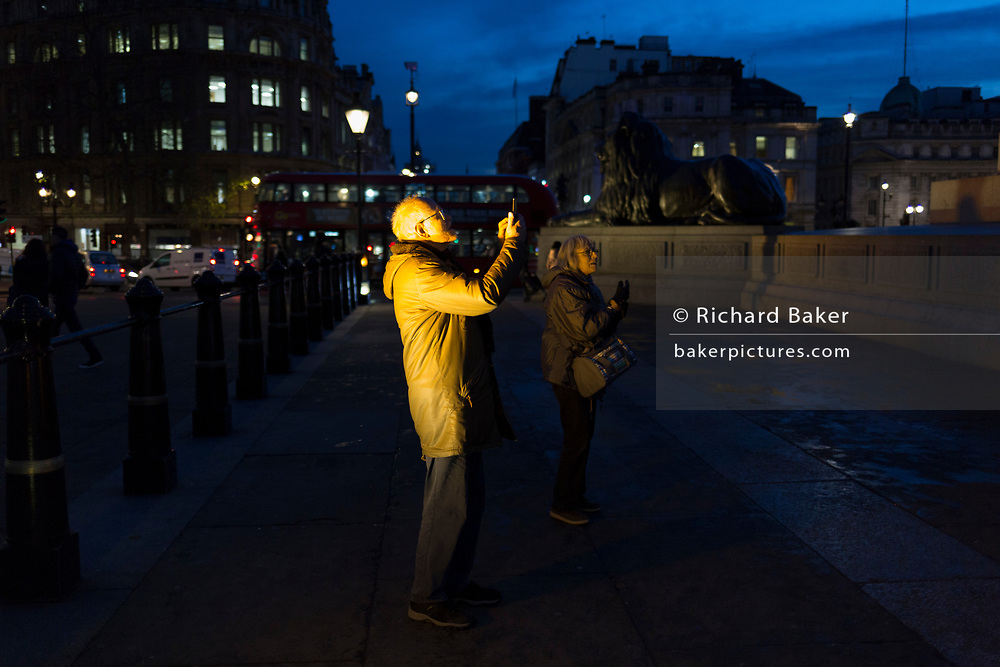 Illuminated by one of four spotlights, a tourist takes photos beneath Nelson's Column in Trafalgar Square, on 12th December 2017, in London England.