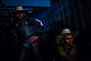 Cowboys wait for their turn on a rodeo show at a livestock compound  in Goiania, Brazil, Friday, Dec. 16, 2016. Considered one of the economic pillars of Brazil, hoarding increasingly huge swaths of land and spreading the same amounts of environmental degradation and land conflicts, the powerful agribusiness finds its heart, soul and voice in the city of Goiânia. Home of a million and a half souls it sits on the immense central plains of Brazil and nurtures a rodeo culture and cowboy lifestyle challenging its own urbanization, highlighting the archaic and rural character of Brazilian mindset and its society. Using cheap videoclips and broadcasting his tunes during rodeos he is invited, Lima showcases the maximum exponent of this  mentality. (Dado Galdieri for the New York Times)