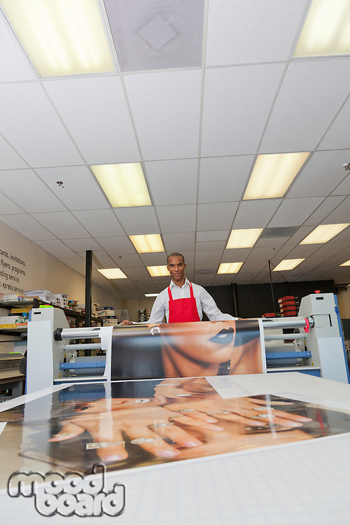 Worker taking printouts at printing press