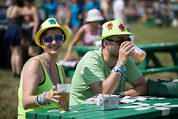 Image ©Licensed to i-Images Picture Agency. 18/07/2014  Henham Park , Suffolk, United Kingdom. A couple wearing matching hats enjoy a beer at Henham Park on what is forecast to be the hottest day of the year so far with temperatures due to hit 30 degrees centigrade. The Latitude Festival of music and arts. Picture by Joel Goodman / i-Images
