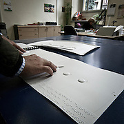 Produzione di pannelli di resina nel laboratorio dell'Istituto dei Ciechi a Milano, seguendo i criteri dell'alfabeto Braille. Con questi pannelli i ciechi possono leggere, e conoscere i monumenti attraverso il tatto..Il sistema solare in rilievo con Plutone visibile a destra e la spiegazione in Braille in primo piano, invece Saturno è sotto le dita. .Production of resin panels in the laboratory of the Institute of the Blind people to Milan, following the criteria of the Braille alphabet. With these panels the blind people can read and know monuments through the tact..The solar system in relief with Pluto visible to right and the explanation in Braille in first floor. The planet under the fingers is Saturn.