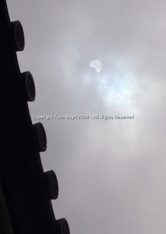 This view shows a rare glimpse in Tokyo during of the July 22, 2009 solar eclipse that passed over Eastern Asia and the Pacific region. Although Tokyo only experienced a 75% partial eclipse, with a total eclipse visible in Iwo Jima and a small chain of islands between Kyushu and Okinawa, the eclipse was almost impossible to see everywhere in Japan due to rain and cloud cover. This very rare view was made during a few brief seconds when the sun became visible at 12:04 PM Tokyo time. It was taken under the at the Otemon Gate which is part of the Edo Castle complex and the Imperial Palace. The circular objects on the left are roof tiles covering the gate and are classic feudal era architecture.