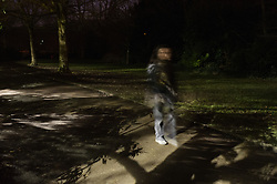 Young women walking in a park at night