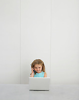 Small girl by desk using cell phone and laptop