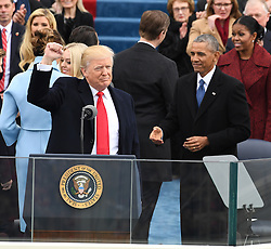 January 20, 2017 - Washington, District of Columbia, U.S. - President DONALD J. TRUMP raises his fist after taking Oath of Office at the inauguration, as BARACK OBAMA walks over to congratulate him with a handshake. Trump becomes the 45th President of the United States. (Credit Image: © Pat Benic/CNP via ZUMA Wire)