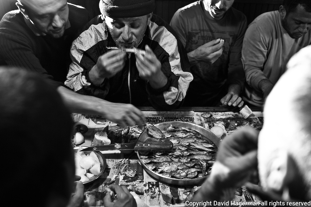 Crew of a Turkish fishing vessel dig into a dinner prepared in the ship's galley. Black Sea, Turkey