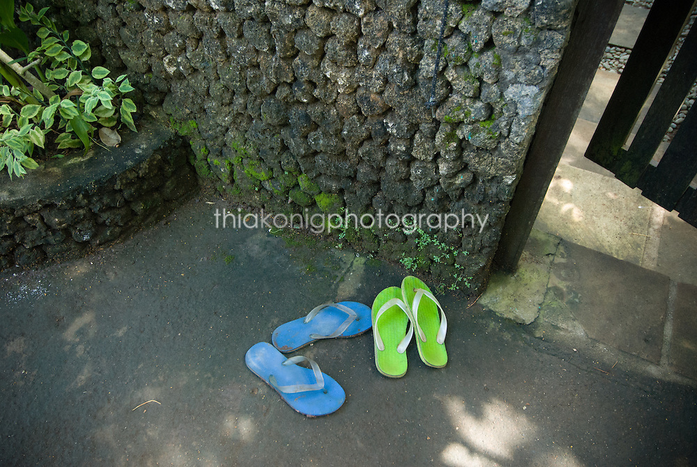 A pair of blue and green flip flop sandals are left outside a garden gate in Bali. It is customary to take ones shoes off before entering a home.