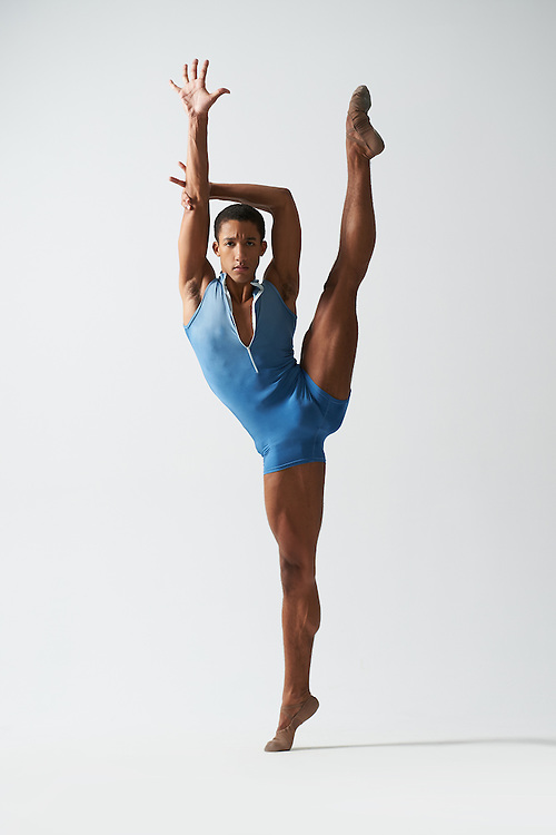 Classical male ballet dancer, Harper Watters, in a blue Yumiko leotard in a la seconde pose in the photo studio on a gray background. Photograph taken in New York City by photographer Rachel Neville.