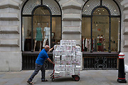 A trolley of toilet rolls are pushed by a sanitation supplies delivery man in the City of London, the capital's Financial district, on 4th June 2018, in London, England.