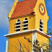San Bernardo Church&rsquo;s Clock Tower in Kralendijk, Bonaire<br /> This striking yellow and orange clock tower is the crown of San Bernardo, one of three Catholic churches in Bonaire and the only one in Kralendijk. Two previous churches honoring St. Bernard were constructed on this site: one in the 18th century and the second in 1829. This replacement was built in 1948.