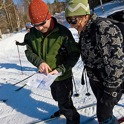 Cross-country skiers checking a map on a backcountry trail near Greenville, Maine.  Shaw Mountain Trail.