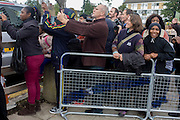 Locals from the Loughborough Estate try to catch a glimpse of the Queen as she makes a brief visit to the Ebony Horse Club at Loughborough Junction, Brixton, London. Accompanied by the Duchess of Cornwall, Her Majesty watched an equestrian demonstration in one of the most disadvantaged inner city neighbourhoods in the country where there is a historic legacy of under-achievement in schools, high rates of teenage pregnancy and negative stereotypes of young people, gang violence and drug related crime.