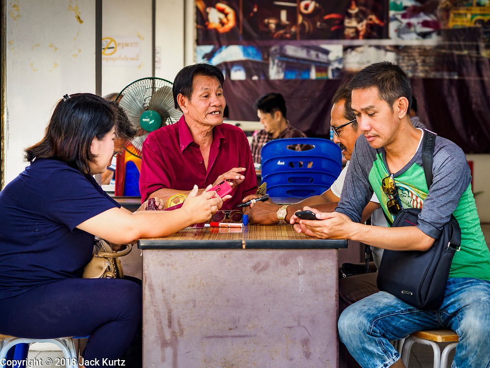22 DECEMBER 2018 - CHANTABURI, THAILAND: Thai gem merchants chat before opening their shop in the gem market in Chantaburi. The gem market in Chantaburi, a provincial town in eastern Thailand, is open on weekends. Chantaburi used to be an active gem mining area in Thailand, but the mines are played out now. Now buyers and sellers come from around the world to Chantaburi for the weekend market. Many of the stones come from Myanmar, others come from mines in Afghanistan and Africa.     PHOTO BY JACK KURTZ