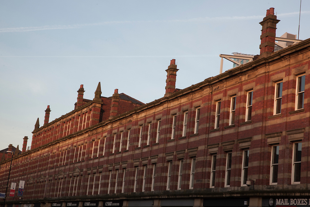 Traditional red brick buildings with old chimneys on Deansgate Street in Manchester, UK.